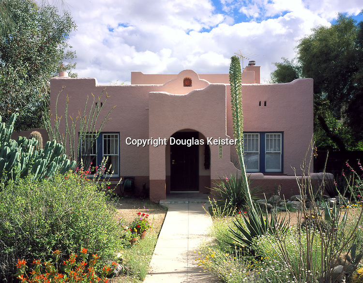 Simple and inexpensive details, such as the meandering parapet and the tiny espadaña and belfry at center, transform this diminutive Tucson cottage dating from 1927 into a gem of Pueblo Revival design.  The espadaña, or curvilinear gable, was an enormously popular Mission Revival motif stemming directly from Spanish Colonial mission churches.  The detail became increasingly familiar to the public following the restoration of such landmark mission churches as the Alamo, which was acquired by the State of Texas as a historic site in 1883, and California's Mission San Carlos Borroméo del Carmelo, whose restoration was begun the following year.  Inexpensive to build, and often embellished with a quatrefoil window inspired by San Carlos Borroméo, the espadaña became a sort of contractor's shorthand for Mission Revival design.  The paired rectangular attic vents surmounting each pair of windows are cleverly improvised from pieces of structural terra cotta, a hollow clay building block commonly used in commercial work of the period.  A buff-and-tan color scheme and a proliferation of succulents complete a classic Southwestern ensemble.