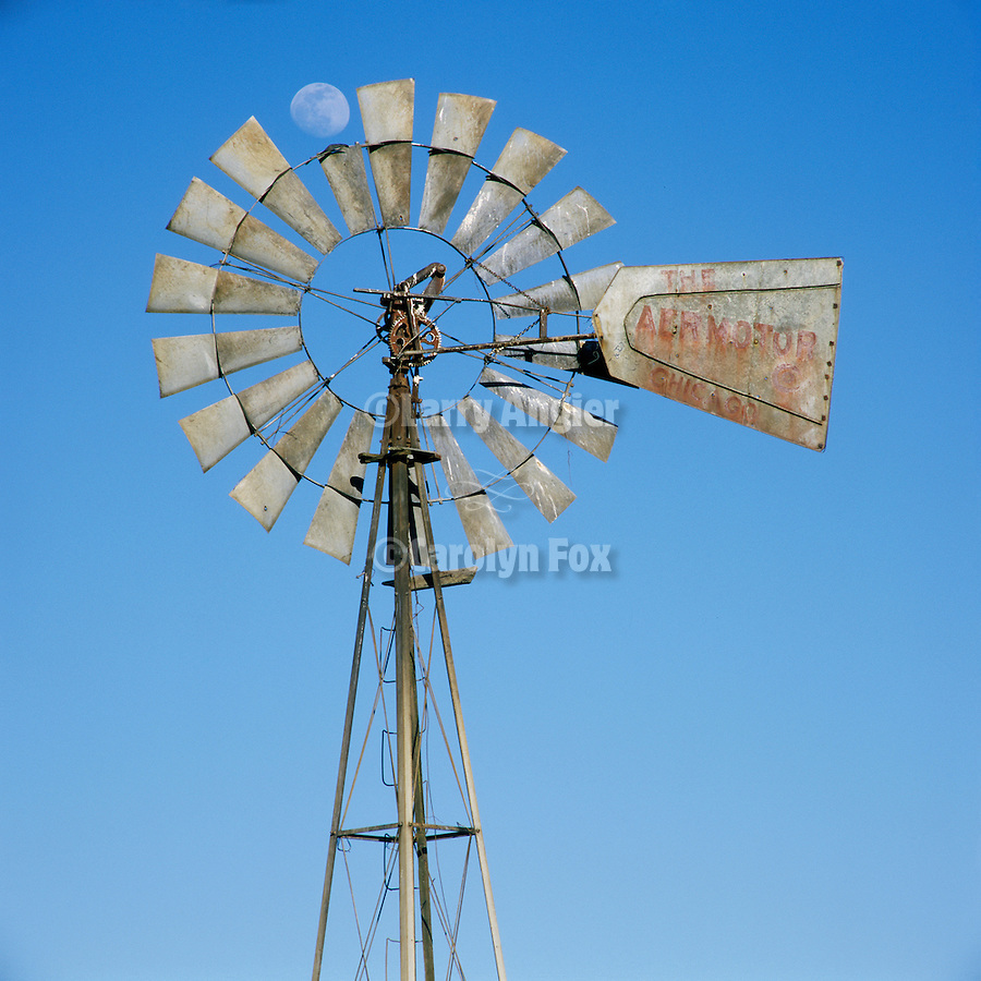 Rusted Pumping Aermotor windmill with waxing moon replacing the broken sail, blue sky, Calaveras County, Calif.