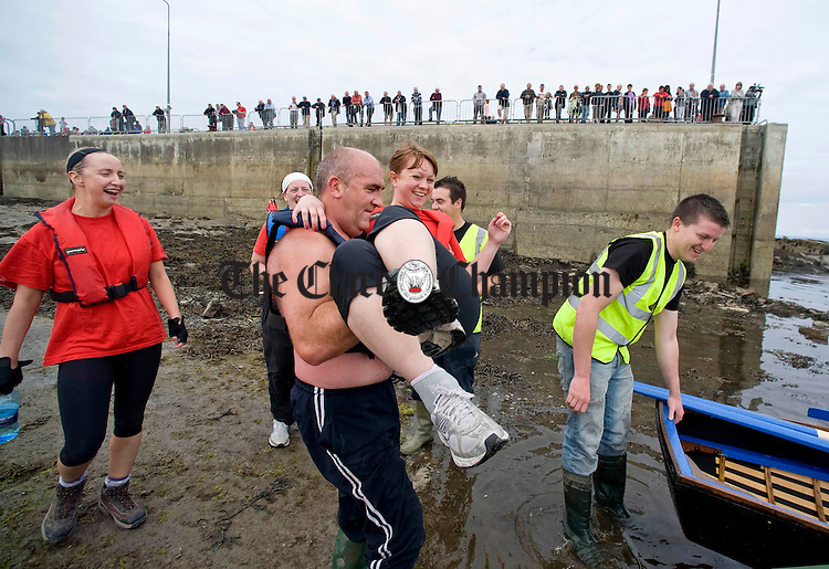 Michael Grimes from Limerick helps Claire Neylon from Clarecastle to her currach during the All Ireland currach racing championships in Doonbeg. Photograph by Declan Monaghan