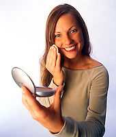 A young woman applies make-up to her face
