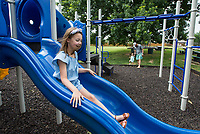 Audrey Killebrew, 7, slides Friday, June 26, 2020, on the playground at the park in their Bentonville neighborhood. Go to nwaonline.com/200627Daily/ to see more photos.<br /> (NWA Democrat-Gazette/Ben Goff)