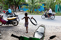 A young boy plays with a bike inner tube in the Tuvaluan capital of Funafuti. Located in the South West Pacific Ocean, Tuvalu is the world's 4th smallest country and is one of the most vulnerable to climate change impacts including sea level rise, drought and extreme weather events. Tuvalu - March, 2019.