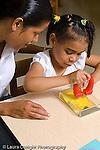 preschool Headstart 3-5 year olds female teacher working with girl using magnet