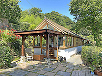 BNPS.co.uk (01202) 558833. <br /> Pic: LillicrapChilcott/BNPS<br /> <br /> Pictured: The Hut. <br /> <br /> A pretty wooden cottage with spectacular panoramic sea views is on the market for £595,000.<br /> <br /> The aptly-named The Hut is an eco-built property set on a hill in the hugely sought-after Cornish village of Mousehole.<br /> <br /> The small but perfectly-formed home looks down over Mousehole harbour and across Mounts Bay to St Michael's Mount.