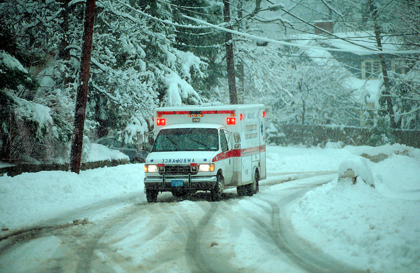 Ambulance driving in heavy snowstorm.