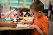 MR / Schenectady, NY. Zoller Elementary School (urban public school). Kindergarten inclusion classroom. Student (boy, 5, with hearing aid) is being assessed on kindergarten math skills. MR: Sch20. ID: AM-gKw. © Ellen B. Senisi.