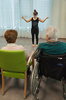"Switzerland. Canton Ticino. Gordola. Casa Riposo (Retirement Home) Solarium. MOPS_DanceSyndrome is an independent Swiss artistic, cultural and social organisation operating in the field of contemporary dance and disability. It is composed only of Down dancers. Elisabetta Montobbio on stage during ""Choreus Numinis""  show. Down syndrome (DS or DNS), also known as trisomy 21, is a genetic disorder caused by the presence of all or part of a third copy of chromosome 21 It is usually associated with physical growth delays, mild to moderate intellectual disability, and characteristic facial features. A group of elderly people, all seated in wheelchairs, look at the woman dancing. A retirement home – sometimes called an old people's home or old age home - is a multi-residence housing facility intended for the elderly. Gordola is a municipality in the district of Locarno. 29.11.2019 © 2019 Didier Ruef"