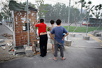 """CHINA. Beijing. Men peer through a fence, trying to catch a glimpse of the new Olympic park. In recent years construction has boomed in Beijing as a result of the country's widespread economic growth and the awarding of the 2008 Summer Olympics to the city. For Beijing's residents however, it seems as their city is continually under construction with old neighborhoods regularly being razed and new apartments, office blocks and sports venues appearing in their place. A new Beijing has been promised to the people to act as a showcase to the world for the 'new' China. Beijing's residents have been waiting for this promised change for years and are still waiting, asking the question """"Where's the new Beijing?!"""". 2008"""