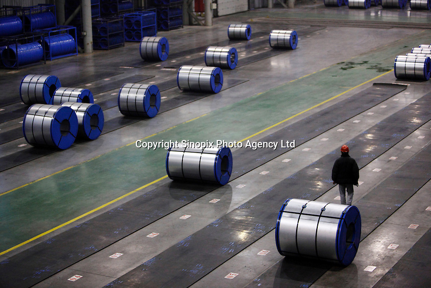 A worker walks through newly made rolls of steel sheets at Ma Steel's new plant in Maanshan, China..29 Dec 2008