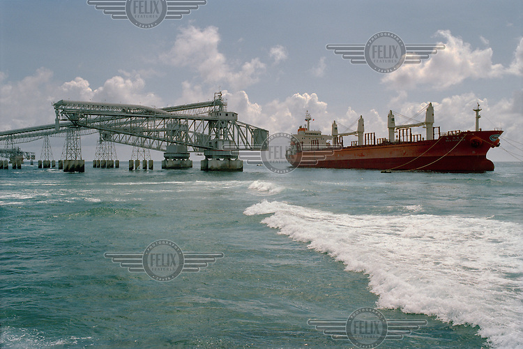 A ship loaded with phosphate from the Nauru Phosphate Corporation (NPC) factory prepares to leave Nauru. The phosphate was loaded for export via a rail line connected to a large cantilever that extends out to ships anchored beyond the reef.