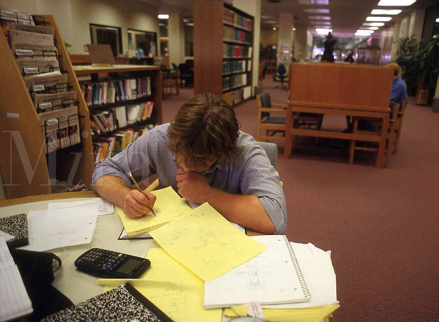 A college student studies at the library. Wesleyan University.