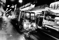 Switzerland. Geneva. Garbage collectors. Streets cleaning.  A worker drives a street brooming machine in the early morning, while a public bus (TPG) is passing with speed.  Night time. © 1991 Didier Ruef