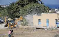 Pictured: A digger is used to demolish part of the house where Ben Needham disappeared from in Kos, Greece. Tuesday 04 October 2016<br />Re: Police teams led by South Yorkshire Police, searching for missing toddler Ben Needham on the Greek island of Kos have moved to a new area in the field they are searching.<br />Ben, from Sheffield, was 21 months old when he disappeared on 24 July 1991 during a family holiday.<br />Digging has begun at a new site after a fresh line of inquiry suggested he could have been crushed by a digger.