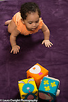 6 month old baby girl crawling toward stack of soft blocks