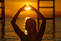 Pictured: Natasha Jenkins makes a heart shape with her hands while in the sea during sunrise as seen through the RNLI boat station in Mumbles, near Swansea, Wales, UK. Sunday 13 June 2021<br /> Re: High temperatures and sunshine has been forecast for most of the UK.