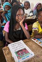 Senegal, Touba.  Young Girl with her Arabic Reader at Al-Azhar Madrasa, a School for Islamic Studies.