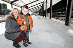 Foto: VidiPhoto<br /> <br /> BARNEVELD – In het buitengebied van Barneveld verrijzen op dit moment twee gloednieuwe kippenstallen van Pluimveebedrijf Beek. Het bedrijf met 39.000 kippen brandde vorig jaar juni af na blikseminslag. Beek was de eerste in Nederland met drie sterren Beter Leven, het keurmerk van de Dierenbescherming. Ook de ultra moderne en beter tegen brand beveiligde stallen (afzonderlijke warmtewisselaars) voldoen aan die hoogste normering. De schuren krijgen een zogenoemde overdekte bosrand. Op 14 mei arriveren de eerste van 40.000 kippen. De daken zijn voorzien van duizend zonnepanelen, waarmee het bedrijf zichzelf volledig van stroom kan voorzien. Beek, die ook een bouwbedrijf heeft, bouwt de stallen zelf. Foto: Eigenaresse Liza Beek met de vijfjarige Lars.