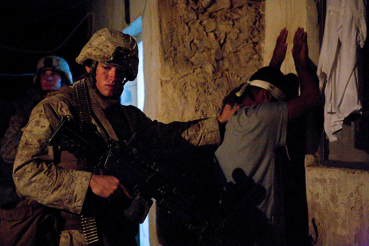21 September 2007, a Marine with 1st Platoon, Charlie Company, 1st Battalion, 7th Marine Regiment guards alleged terrorist Othman Mohammed Rabiah at his house in Hit, Iraq. Meanwhile Marines with 1st Platoon continue to search the house for any weapons or incriminating evidence. Othman Mohammed Rabiah is being detained to be tried for terrorist acts. 1/7 is deployed with Multi National Forces-West in support of Operation Iraqi Freedom in the Al Anbar province of Iraq to develop Iraqi Security Forces, facilitate the development of official rule of law through democratic reforms, and continue the development of a market based economy centered on Iraqi reconstruction. (Official USMC photograph by Cpl. Shane S. Keller)