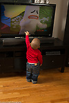 18 month old toddler boy reaching out to touch sad cartoon figure on TV