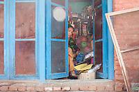 A shop owner looks outside through the door. Shanku, near Kathmandu, Nepal. May 9, 2015
