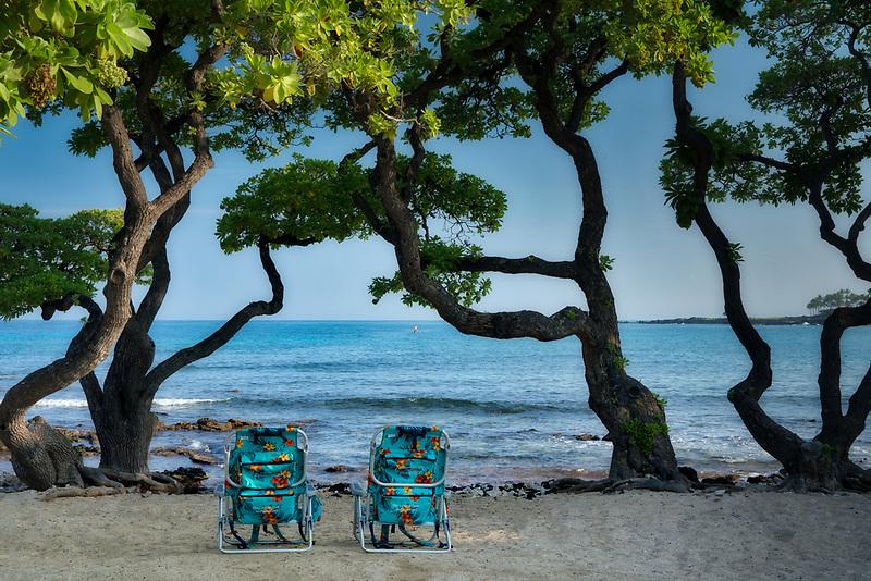 Two chairs on beach with heliotrope trees. Keokea Beach. Hawaii, The Big Island