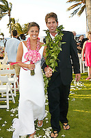 Bridal couple walking down the aisle wearing maile and flower leis and slippers