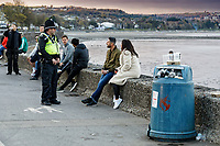 Pictured: A police officer speaks to two people sitting outdoors in Mumbles. Friday 16 April 2021<br /> Re: People enjoy an evening out after Covid-19 lockdown rules were relaxed, in Swansea Bay, Wales, UK.