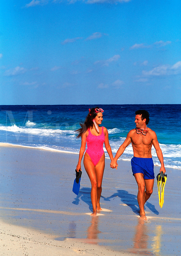 Couple on beach with snorkeling equipment