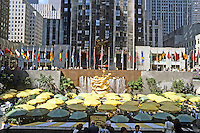 """New York City: Rockefeller Plaza--restaurant, skating rink and a colorful display of flags with skyscrapers surrounding the plaza. """"Prometheus"""" on display."""