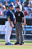 Asheville Tourists manager Warren Schaeffer (13) discusses a controversial call with home plate umpire Anthony Perez during a game against the West Virginia Power at McCormick Field on June 25, 2016 in Asheville, North Carolina. The Tourists defeated the Power 8-4. (Tony Farlow/Four Seam Images)