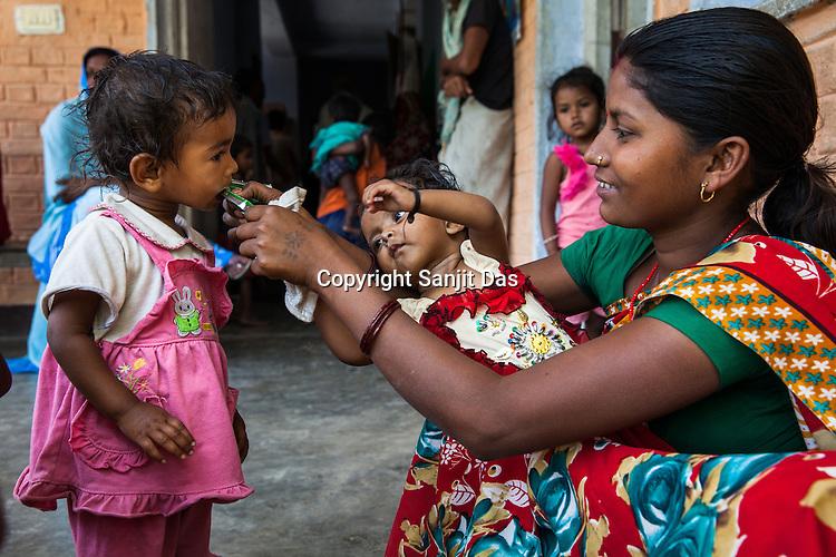 21 year old Asha Devi feeds RUTF to a neighbour's daughter at the government health centre in  Hanuman Nagar, Saptari, Nepal.