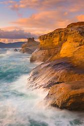 Crashing waves along sandstone cliffs on Cape Kiwanda at sunset.