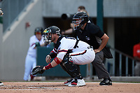 Charlotte Knights catcher Yasmani Grandal (17) sets a target as home plate umpire Jonathan Parra looks on during the game against the Norfolk Tides at Truist Field on August 22, 2021 in Charlotte, North Carolina. (Brian Westerholt/Four Seam Images)