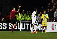 Swansea, UK. Thursday 20 February 2014<br /> Pictured: Match referee Ivan Bebek (L) shows Lorenzo Insigne of Napoli a yellow card<br /> Re: UEFA Europa League, Swansea City FC v SSC Napoli at the Liberty Stadium, south Wales, UK