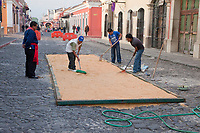 Antigua, Guatemala. Preparing the sawdust base for an alfombra (carpet) of flowers, pine needles, and other traditional materials to decorate the street in advance of the passage of a procession during Holy Week, La Semana Santa.  The alfombra will be finished only a couple of hours before the passage of the procession, after which the remains will be quickly swept away by municipal street sweepers.