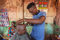 Nigeria. Enugu State. Enugu. Reverend Father Gerald Chukwudi Ani is a catholic priest from the Diocese of Lugano (Ticino, Switzerland). He is back in his hometown and gets an haircut with hair clippers at a local hairdresser. Enugu is the capital of Enugu State, located in southeastern Nigeria.  28.06.19 © 2019 Didier Ruef