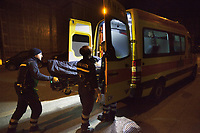Switzerland. Canton Ticino. Lugano. Night scene for a medical emergency intervention. A man lying down on an emergency medical stretcher is being transported by ambulance. Paramedics team need to bring urgently a man with drug abuse to the hospital. Four paramedics wear blue uniforms and work for theCroce Verde Lugano. Both men and the woman (L) are professional certified nurses, the other man (R) is a volunteer specifically trained in emergency rescue. TheCroce Verde Lugano is a private organization which ensure health safety by addressing different emergencies services and rescue services. Volunteering is generally considered an altruistic activity where an individual provides services for no financial or social gain to benefit another person, group or organization. Volunteering is also renowned for skill development and is often intended to promote goodness or to improve human quality of life. 20.01.2018 © 2018 Didier Ruef