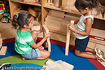 Education Preschool 3-5 year olds block area two girls building with wooden blocks horizontal separately