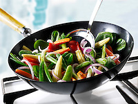 Stirfry vegetables being cooked in a wok