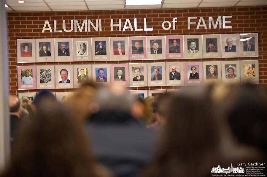 A crowd sits in a room at Westerville High School as the city's school board meets in front of the school's wall of photos for the Alumni Hall of fame to consider budget cuts required by the failure of a $23 million levy and tax increase. One of the cuts expected is sports.