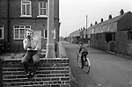 South Kirkby Colliery Yorkshire England. 1979. Girl sitting on wall at end of Club Terrace, and Duke Street with NUM housing.