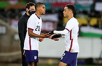 SWANSEA, WALES - NOVEMBER 12: Reggie Cannon #20 and Sergino Dest #2 of the United States shake hands during a game between Wales and USMNT at Liberty Stadium on November 12, 2020 in Swansea, Wales.
