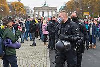 """Sogenannten """"Querdenker"""" sowie verschiedene rechte und rechtsextreme Gruppen hatten fuer den 18. November 2020 zu einer Blockade des Bundestag aufgerufen. Sie wollten damit verhindern, dass es """"eine Abstimmung ueber das Infektionsschutzgesetz"""" gibt - unabhaengig ob es diese Abstimmung tatsaechlich gibt.<br /> Bereits in den Morgenstunden versammelten sich ca. 2.000 Menschen, wurden durch Polizeiabsperrungen jedoch gehindert zum Reichstagsgebaeude zu kommen. Sie versammelten sich daraufhin u.a. vor dem Brandenburger Tor.<br /> Im Bild: Polizeibeamte laufen durch die Demonstranten nund fordern sie auf, eine Maske zu tragen. Die Auffoderung wurde folgenlos ignoriert.<br /> 18.11.2020, Berlin<br /> Copyright: Christian-Ditsch.de"""