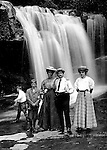 Stewart Township:  View of the Stewart family, Homer Jr, Alice, Homer, Helen, and a Brady cousin posing for a photo in front of a waterfall in Bear Run Creek.  Stewart family went to visit Brady family relatives that lived in Stewart Township.