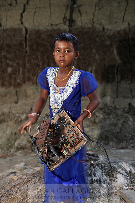 In the village of Sangrampur, a young girl carries a circuit board, which she will deliver to her family nearby who recycle e-waste as a source of income. Kolkata, India. November, 2013