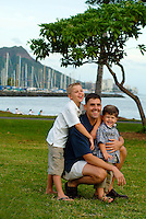 Portrait of father with two sons at magic island park with Diamond head  and Ala Wai yacht harbor in rear