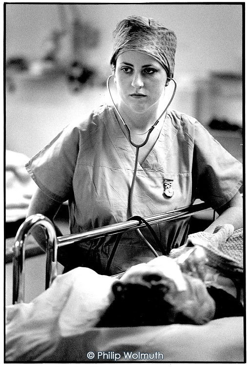 A nurse checks a patient on the post-operative recovery ward, Mayday Hospital, South London.