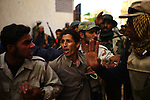 Sirte, LIBYA: Monday 11th October 2011:..A suspected Gaddafi loyalist soldier, center, is taken prionser by rebel fighters. ..Ayman Oghanna