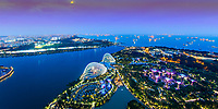 Beautiful, sunset aerial view of gardens by the bay, buildings, and myriads of lit-up containerships from Marina Bay Sand hotel rooftop, Singapore