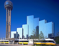 Dallas Area Rapid Transit train pulls out of Union Station, in downtown Dallas, in front of the Dallas Downtown Hyatt. Dallas Texas United States DART Station.